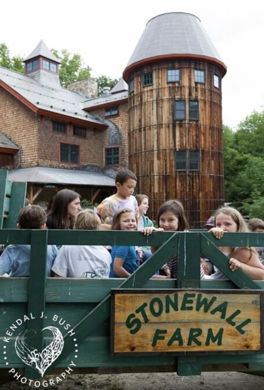 Children in a trailer in front of a barn silo