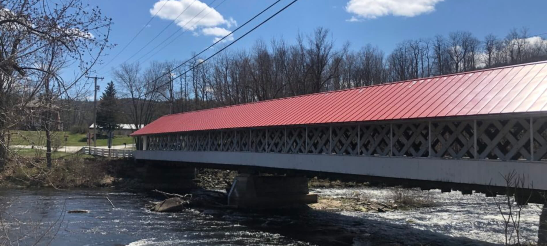 Covered bridge with red metal roof with wooden sides over creek under clear blue skies with fluffy clouds.
