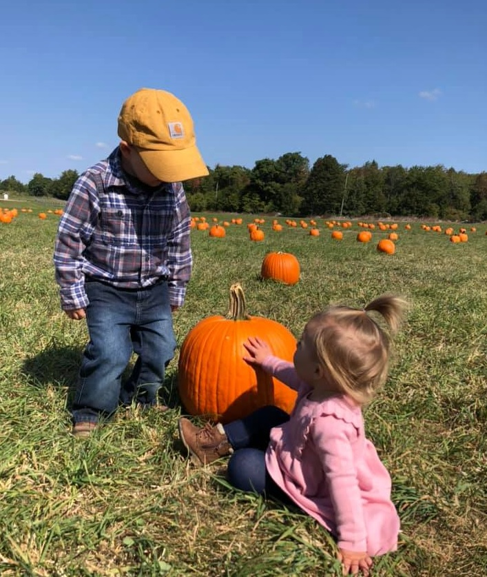 Two young children in a pumpkin patch with vivid blue sky