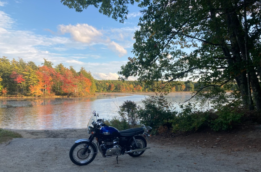 Motorcycle in front of a lake with beautiful fall colors in the background