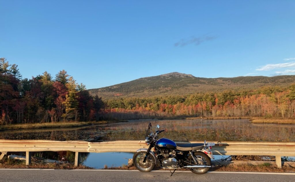 Motorcycle parked near lake with view of Mount Monadnock with fall foliage colors near the base