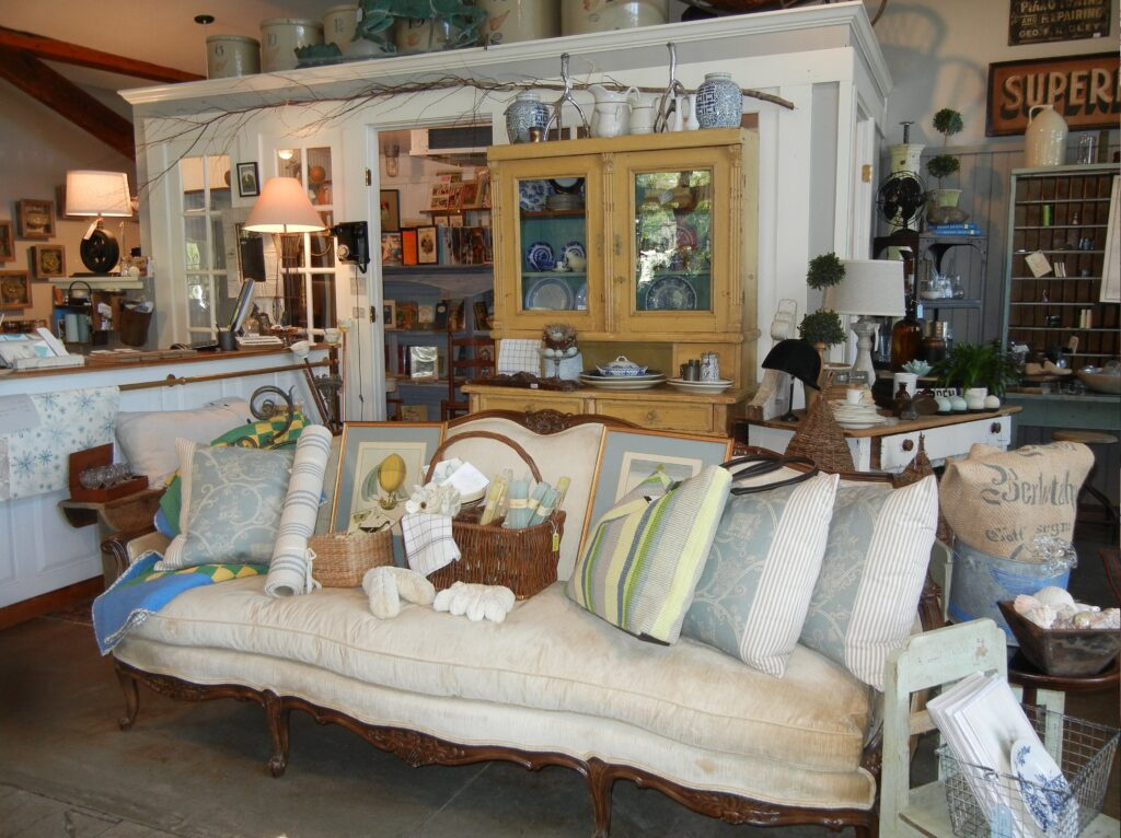 Sofa in foreground surrounded by a china cabinet, lamps, and many antiques at Bowerbird & Friends