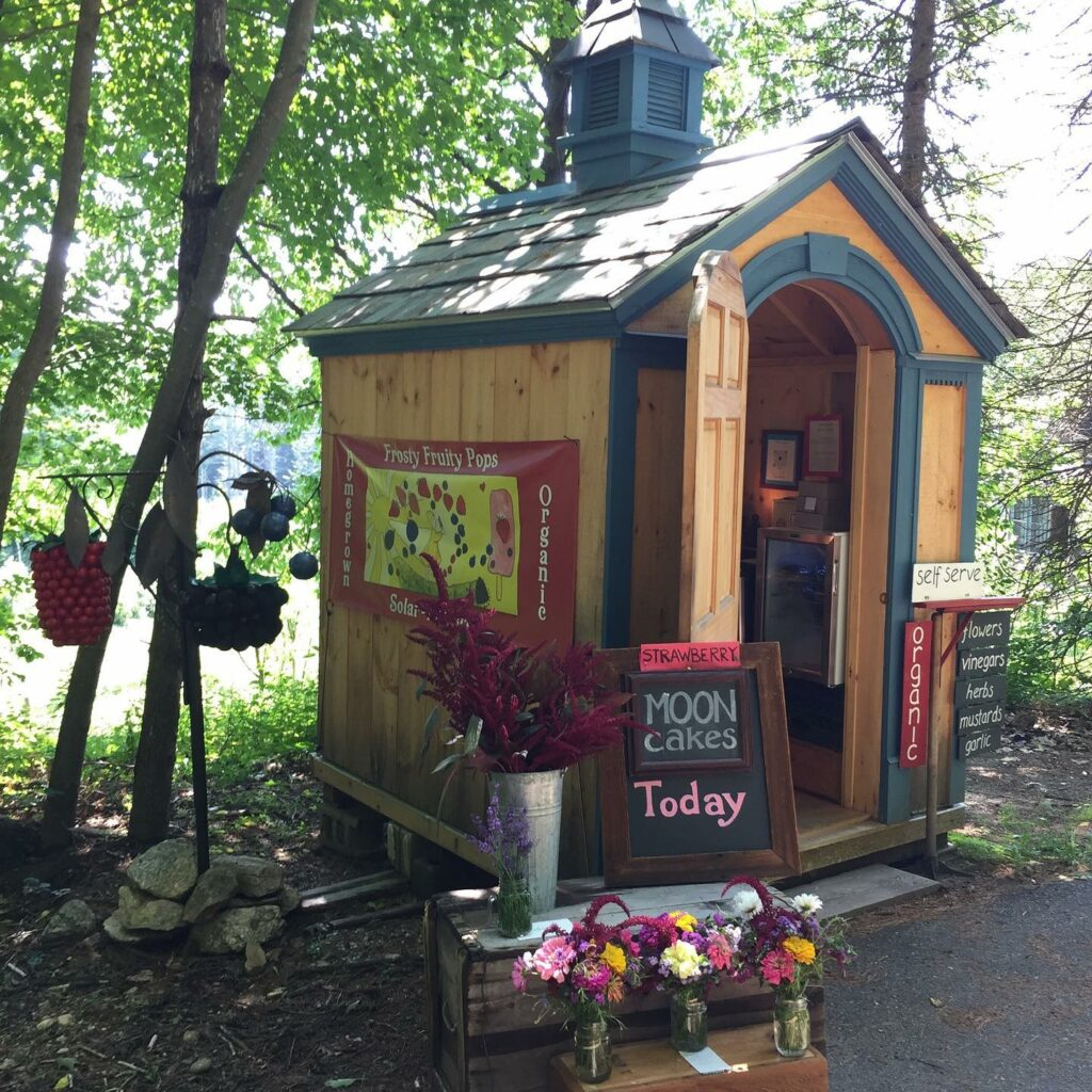 Very small farmstand, called the Tiny Farmstand at Cheshire Garden, shown with bouquets with fresh flowers