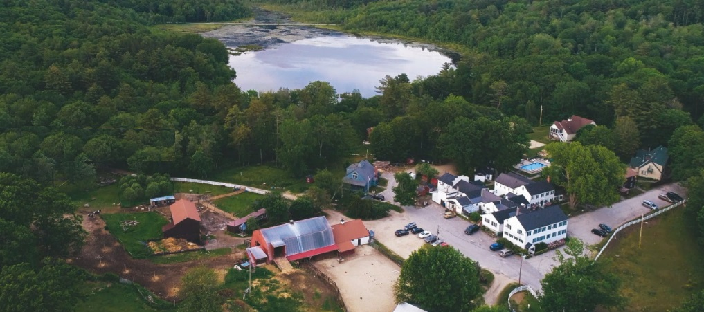 Aerial view of the Inn at East Hill Farm, including farm buildings, pond, and beautiful trees on the property