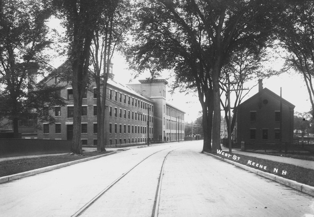 Old photo of Faulkner and Colony Mill from West Street, with railroad tracks and no cars