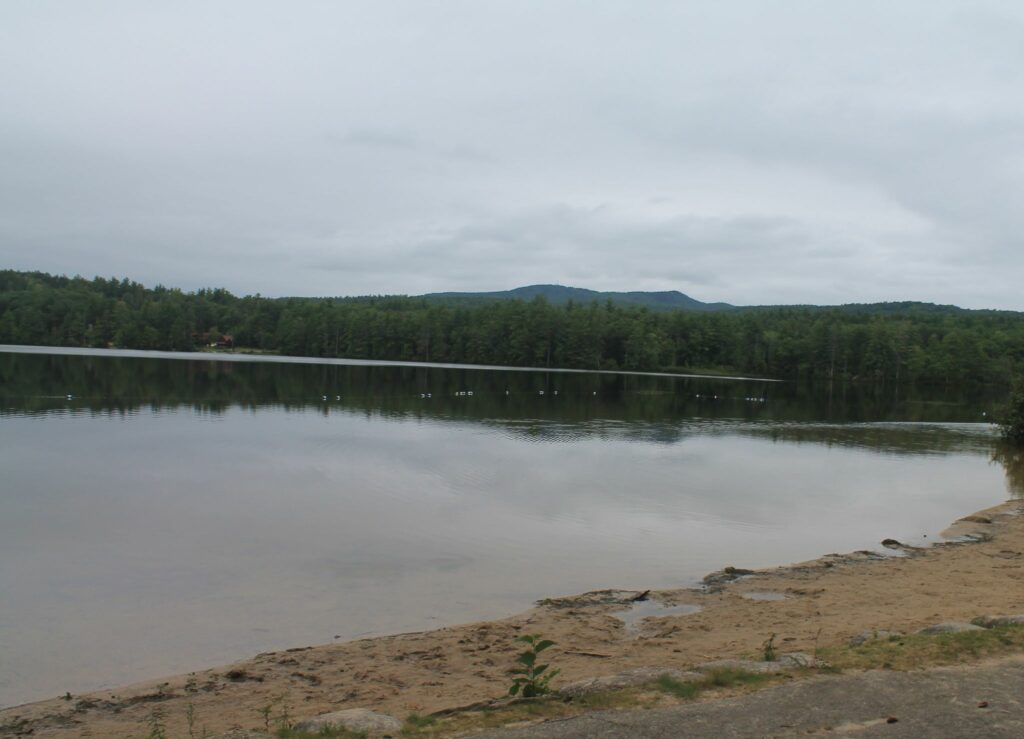 Greenfield State Park, showing sandy beach, lake and hills in the background