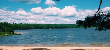 Greenfield State Park with sandy beach, blue sky with clouds, and lake