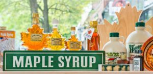 """Maple Syrup"" sign in gift shop, showing jugs of maple syrup and glass bottles of golden maple syrup in the shape of a maple leaf."