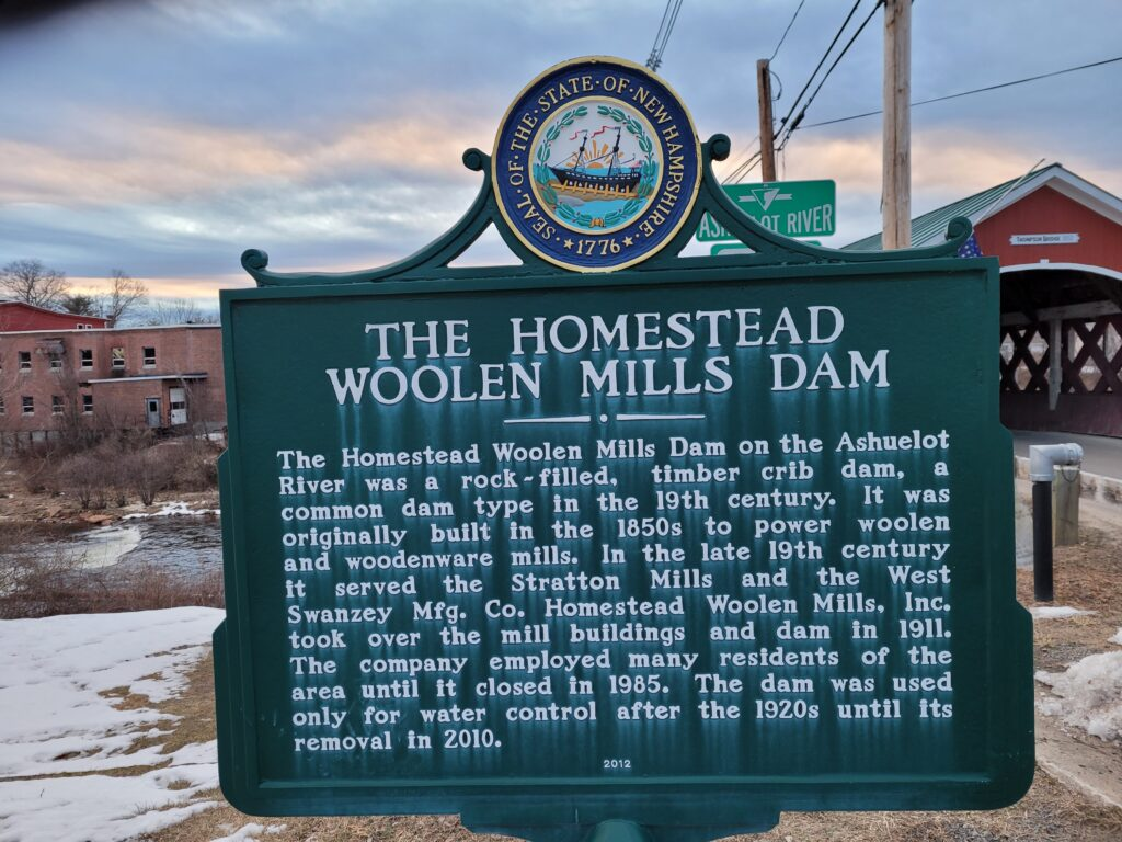 Sign describing the Woolen Mills Dam, with the woolen mills building visible on the left in the background and the Thompson Covered Bridge on the right