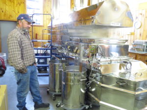 Man monitoring maple syrup being boiled in state-of-the-art equipment