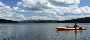 Woman kayaking on lake (the sole person visible) with mountain and forest in the background; blue sky with plenty of cumulus clouds