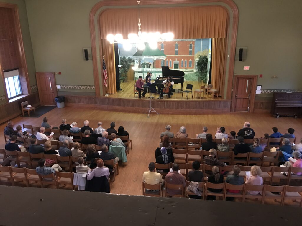 People seated in an auditorium listening to a musical performance