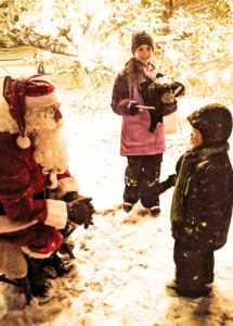 A small boy talks to Santa Clause as his sister looks on