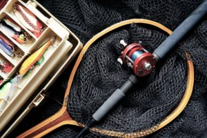 Fishing equipment: fishing rod, net, and a box with lures