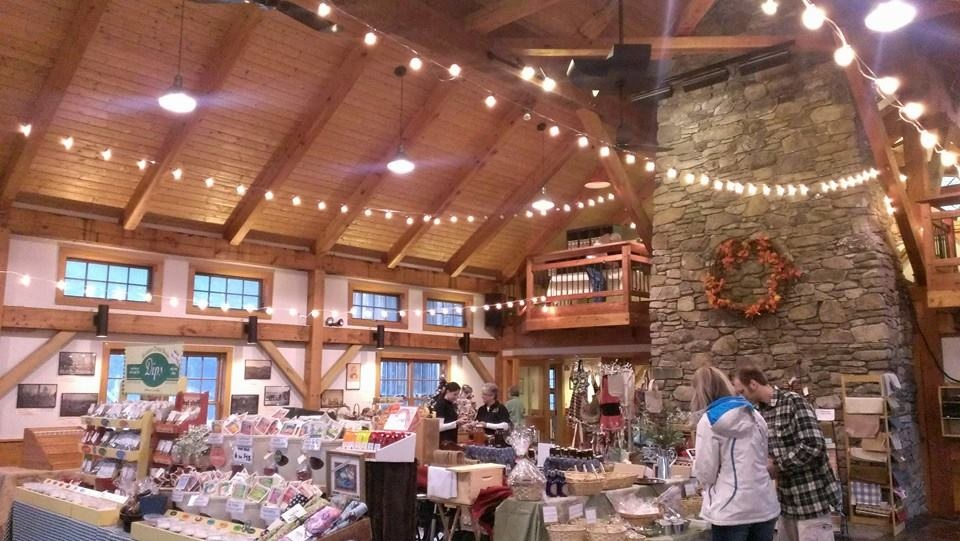 Shoppers browse shelves and baskets full of craft items inside a post and beam barn brightly lit by stings of shite lights