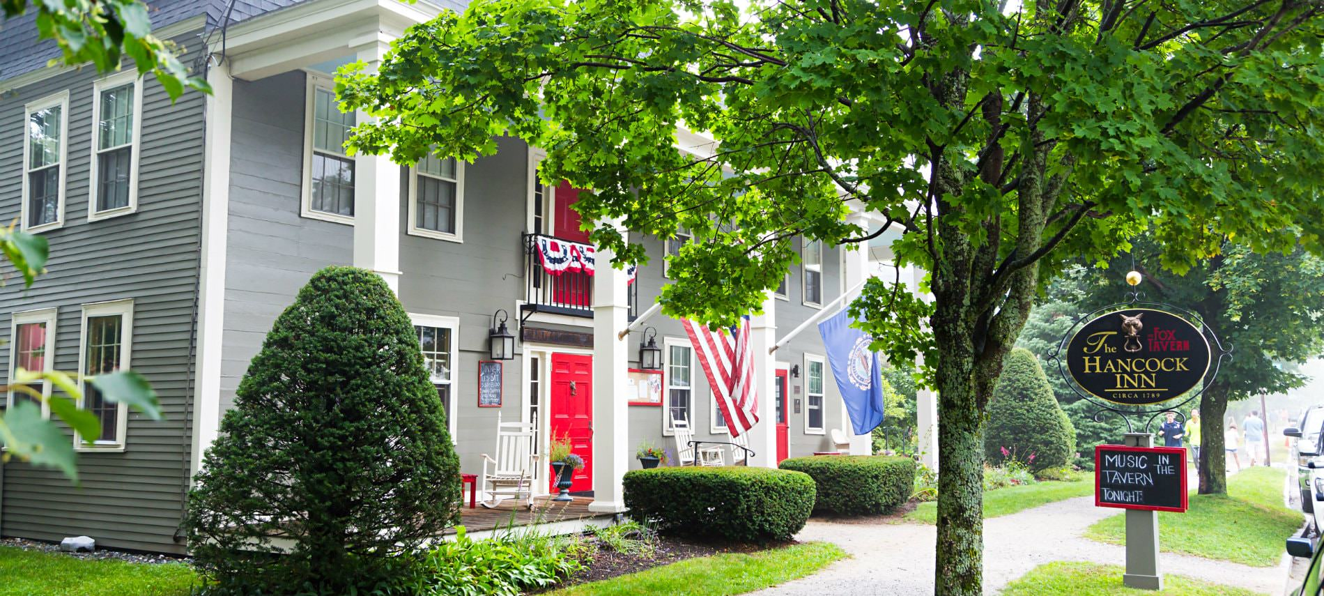Old New England Inn surrounded by many trees and an American flag as well as other flags