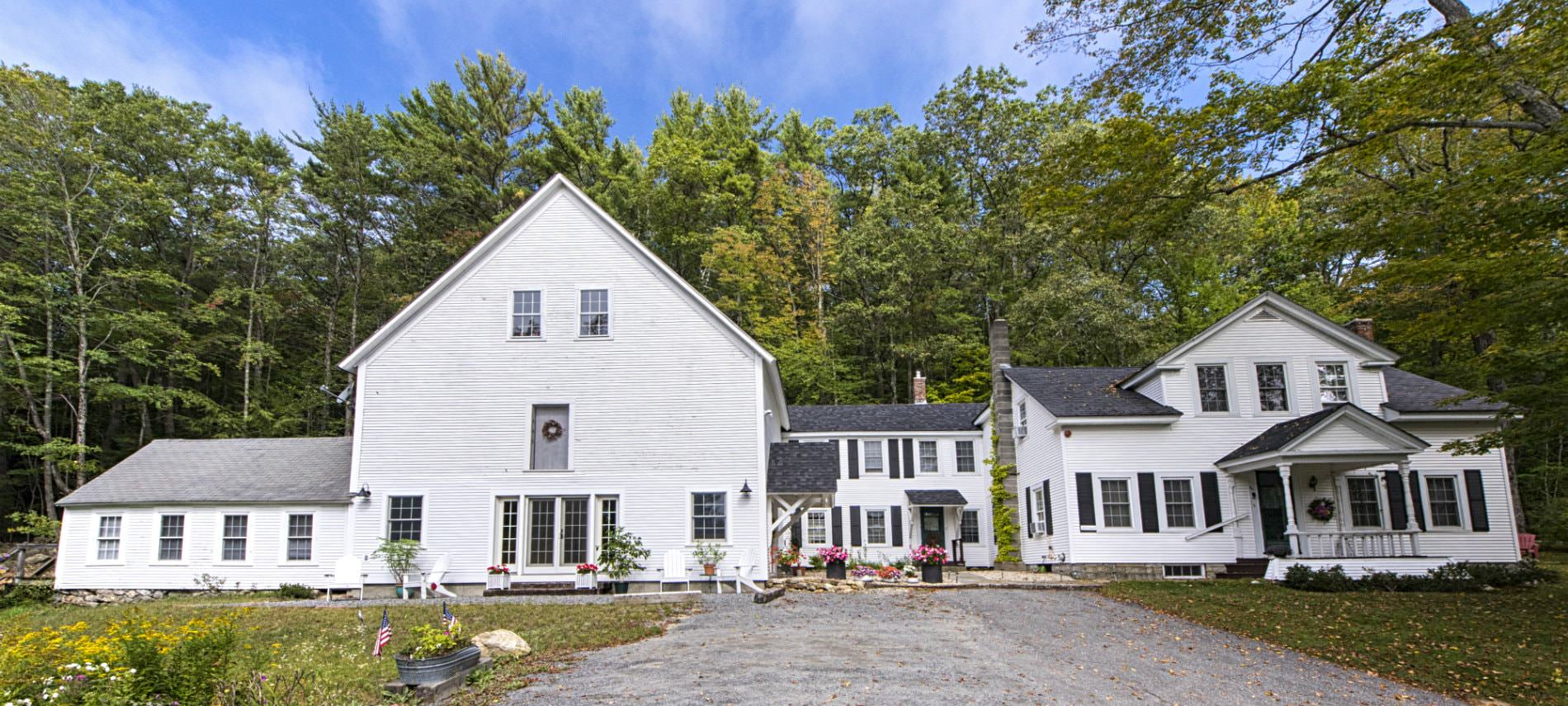 Large white antique house with an attached barn in country setting