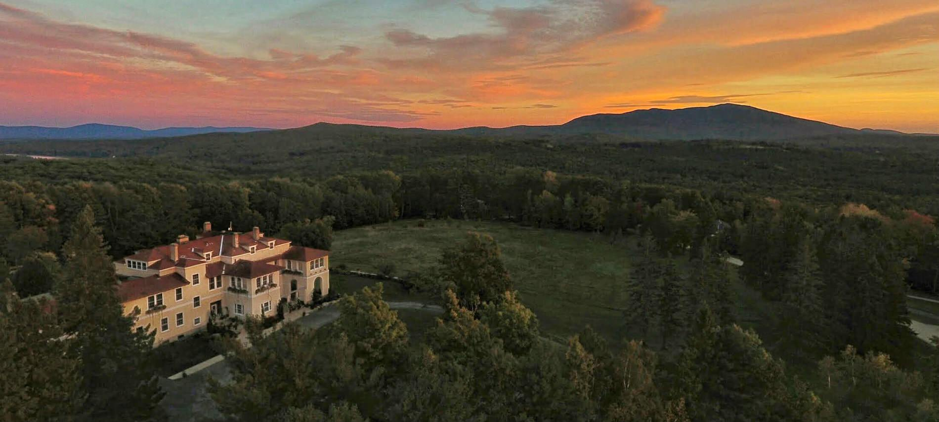 Stunning aerial view of large tan manor house surrounded by lush green lawn, miles of trees, and sun setting over Mount Monadnock