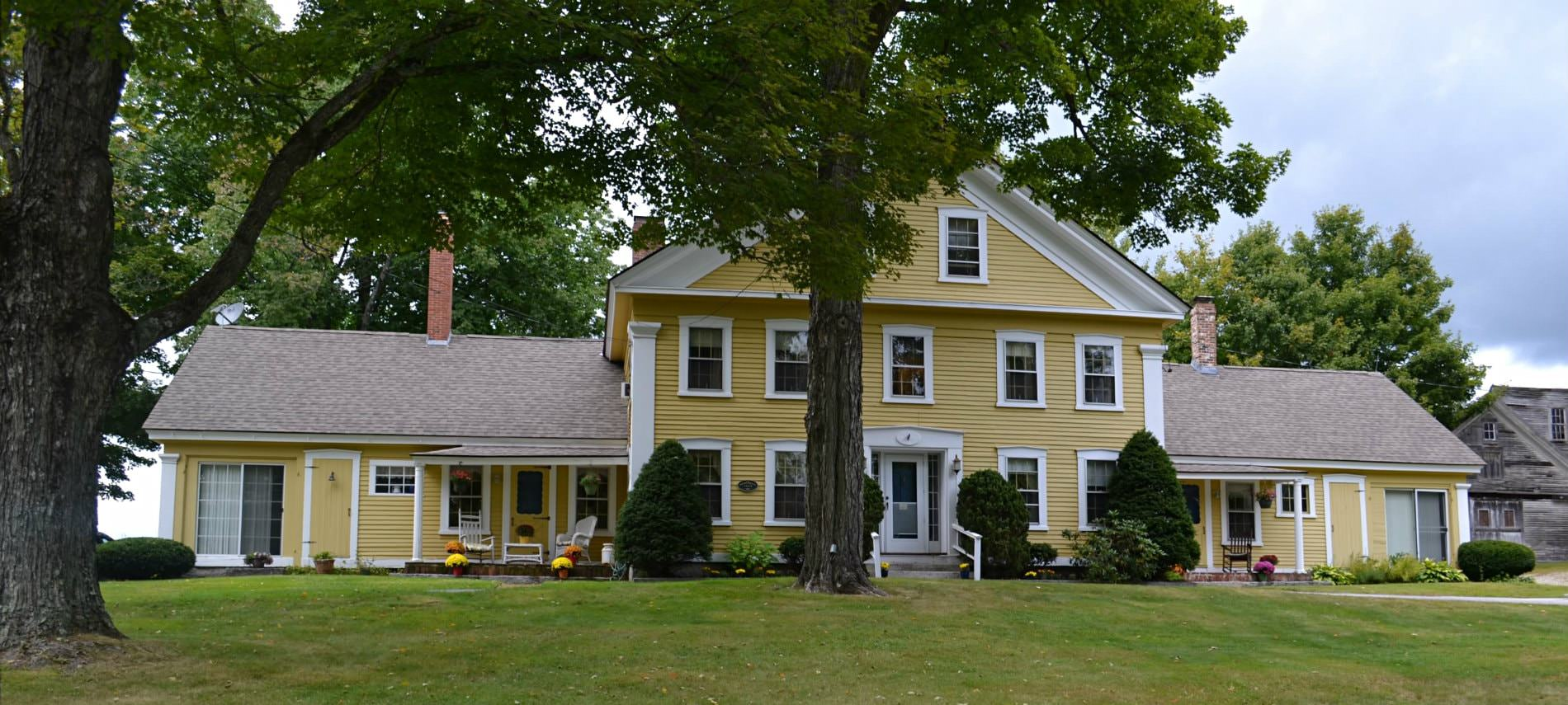 Large yellow sided Benjamin Prescott Inn with green lawn and tall green trees