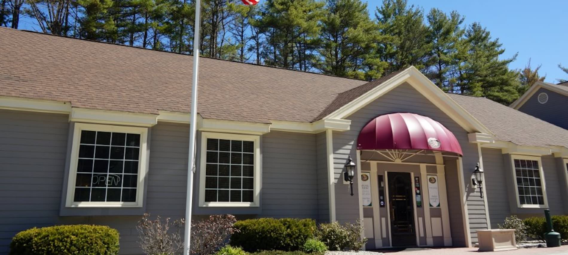 Exterior of Brady's American Grill - sided building with maroon awning, tall pines and blue skies