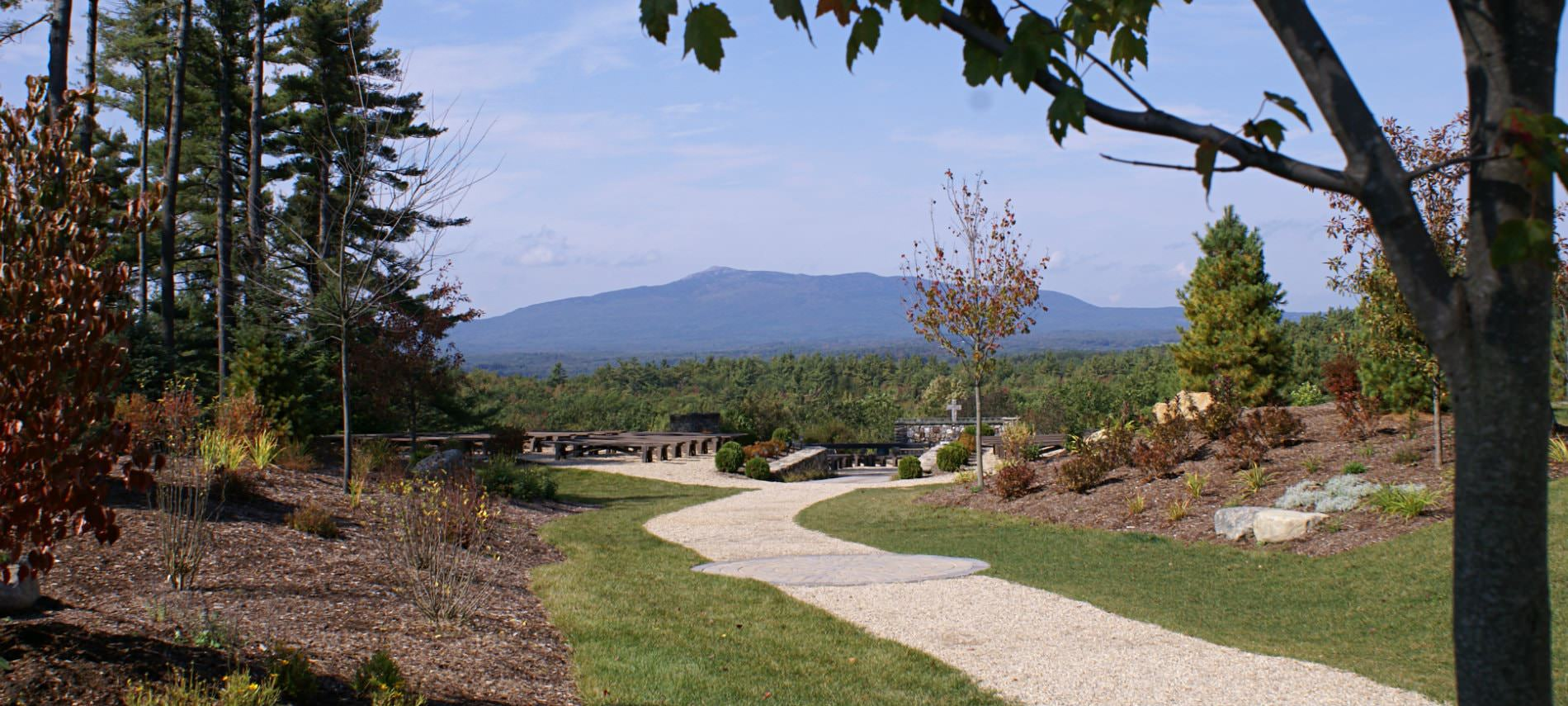 Beautiful property with gravel sidewalk, green grass, mulched landscaping, trees and view of Mount Monadnock
