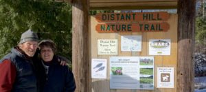 Man and woman standing in front of Distant Hill Nature Trail sign