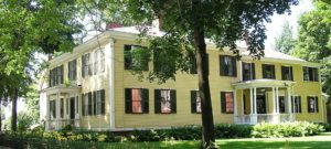 Large yellow sided Horatio Colony House with shuttered windows, green lawn and tall trees