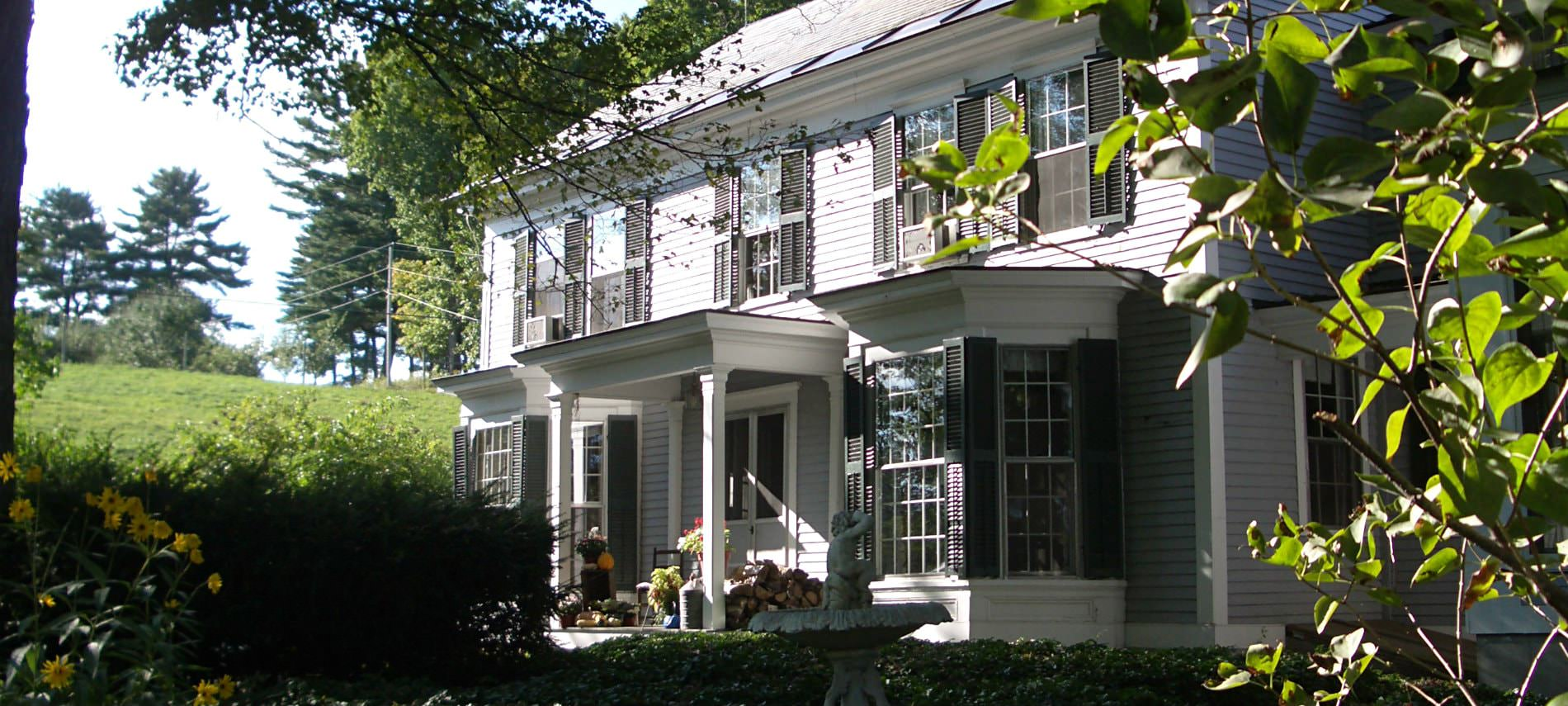 Inn at Valley Farms - white two-story house with covered entry surrounded by greenery