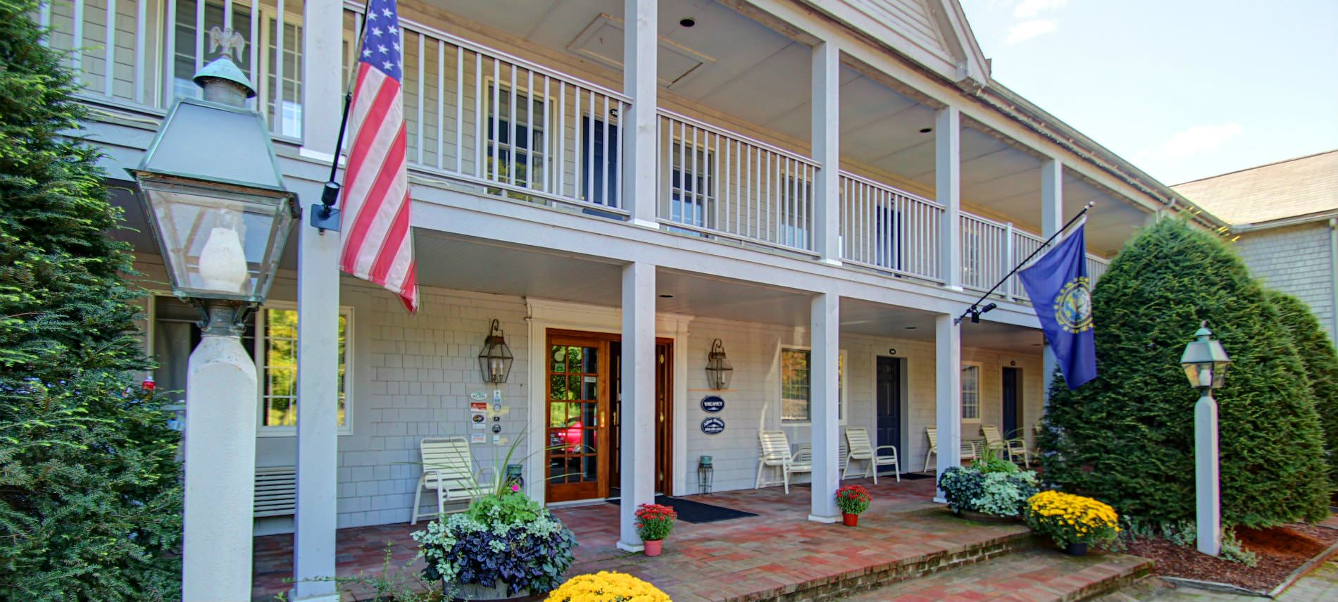 Jack Daniels Motor Inn - large building with two story covered porches, railing and posts and colorful flowers