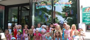 Several smiling children standing in front of Life is Sweet candy story front