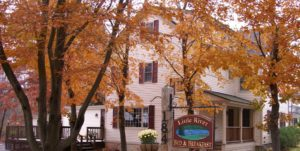 Little River B&B - white sided home in the fall surrounded by trees with orange leaves