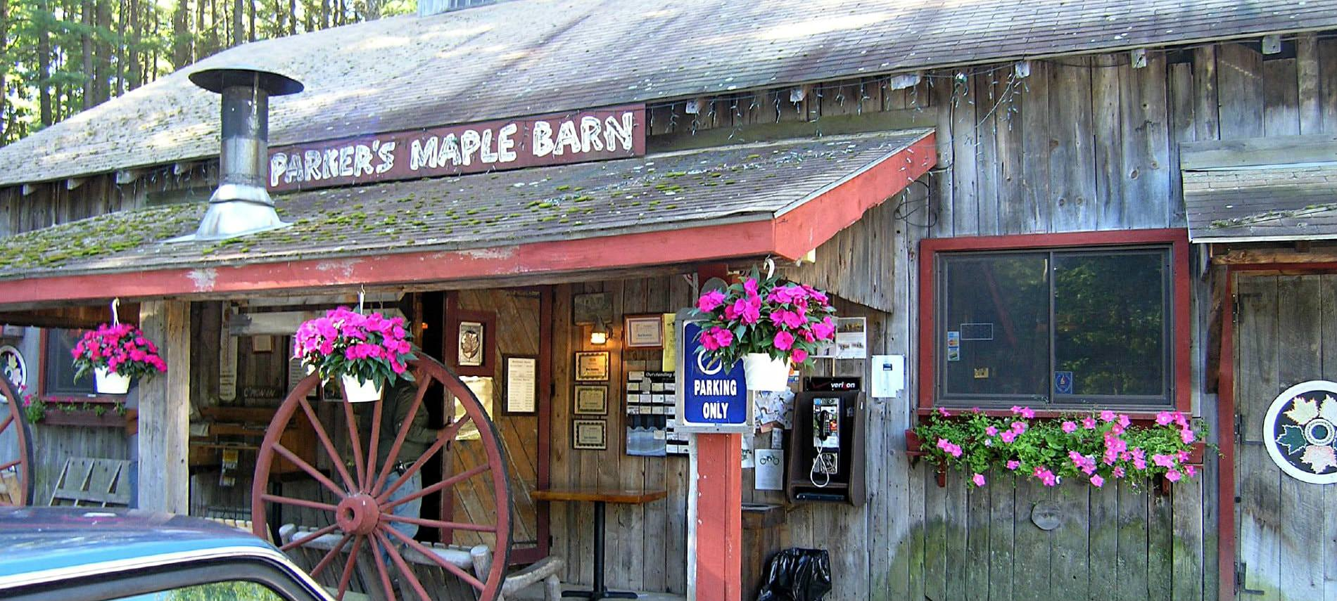 Parker's Maple Barn store front with covered entrance, fresh pink flowers, and wagon wheel