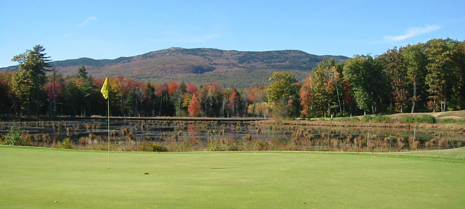 Green grassy golf course with autumn colored trees, blue skies and Mount Monadnock in the background