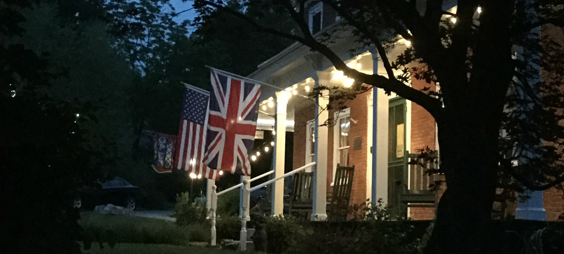 Exterior view of brick Birchwood Inn at dusk with porch lights on