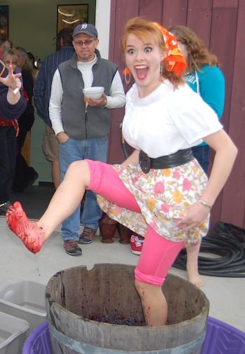 People watching a woman dressed like Lucy Arnez as she stomps grapes in a wood barrel