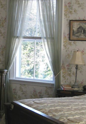 Pretty guest room with floral papered walls, elegant bed with tall arched headboard, bureau with mirror and windows with shears
