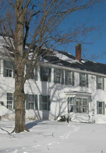 Large white sided Bridges Inn surrounded by snow covered ground, trees and blue skies