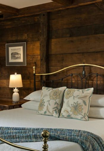 Guest room with black and brass bed with white bedding against a wood plank wall, two nightstands and a window