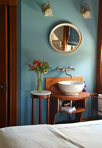 Blue guest room wit wood trim and doors, fireplace, wash basin sink and metal bed
