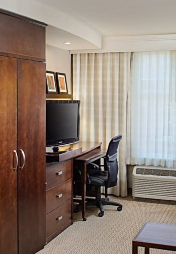 Guest Suite sitting area with sofa and chair, armoire, desk and chair, large window and carpeting