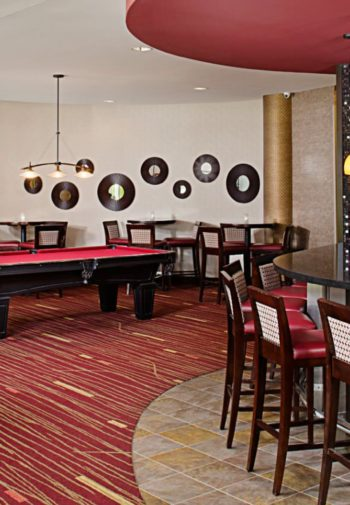 Interior bar area with elegant bar, red stools and pendant lights, pool table, tables and chairs and chandeliers