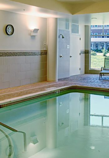 Indoor swimming pool with sconce lighting, large window, lounge chairs and a table and chairs