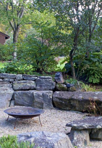Gravel fire pit surrounded by rocks, greenery and brown building in the background