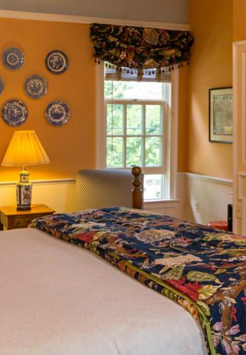 Yellow guest room, two windows, fireplace, sitting chairs and bed with colorful pillows and blanket