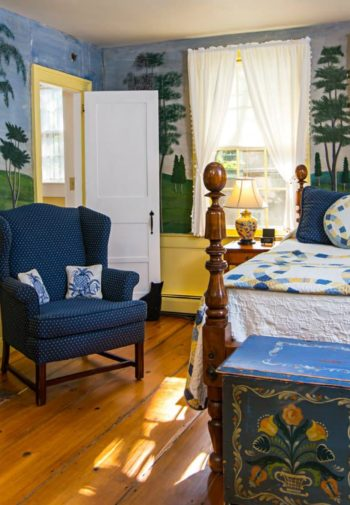 Colorful guest room with wide plank wood floors, countryside mural on the walls, fire stove, chair, bed and chest