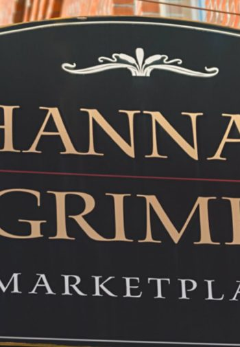 Black and gold Hannah Grimes MarketPlace sign hanging outside brick storefront