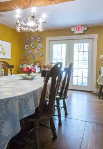 Spacious yellow dining room with wood floors, oval dining table and hutch, and beverage buffet table