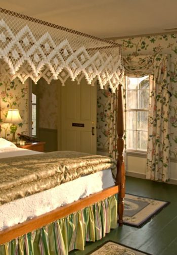 Spacious guest room with floral papered walls, large lace top canopy bed, windows, wood floors and table and chairs