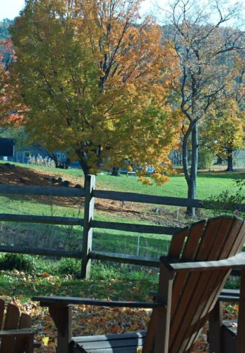 Adirondack chairs overlooking grassy fields, tree-covered hills, and autumn colored trees