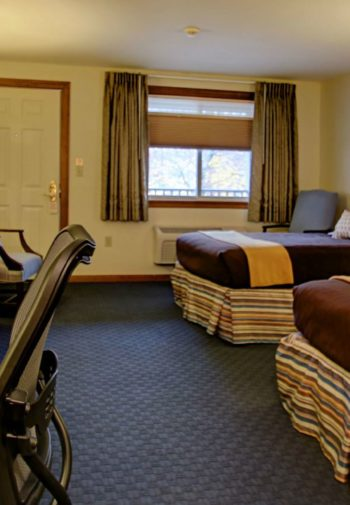 Spacious guest room with two large beds, desk and chair, fridge and microwave, double window and carpeting